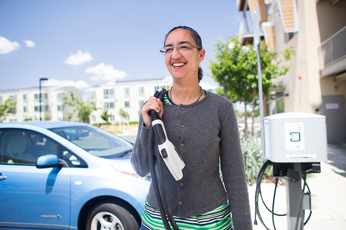 Dahlia Garas plugging in her electric vehicle at UC Davis' West Village