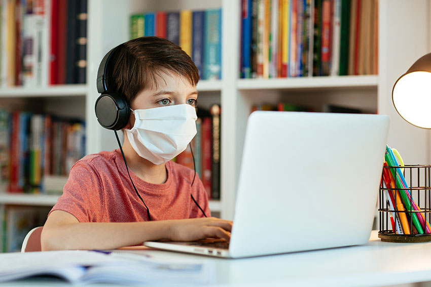 Boy in face mask working on a computer