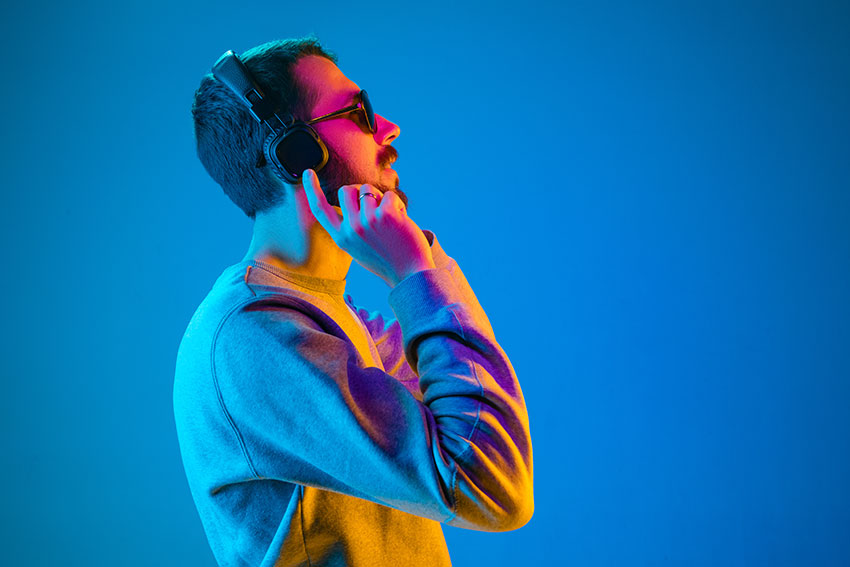 Young man listening to music with headphones on.