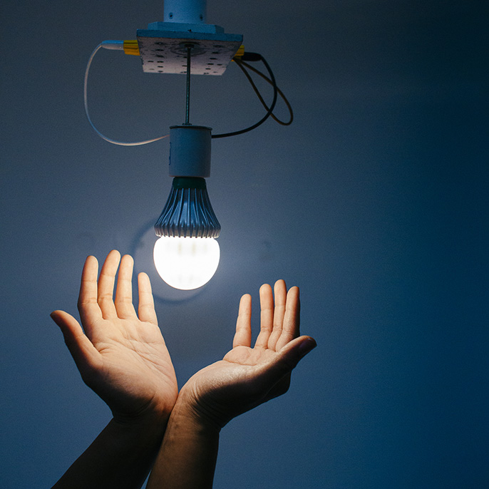 Hands below a light bulb
