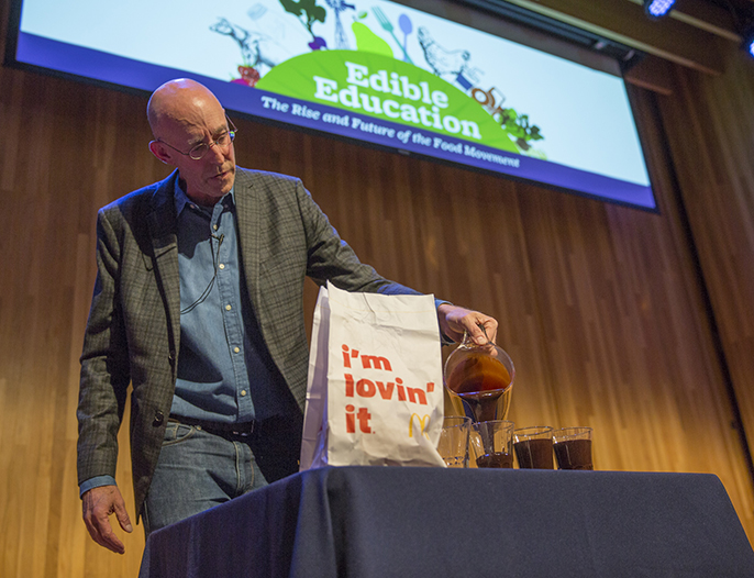 Michael Pollan makes a point about the amount of oil it takes to produce a hamburger during an Edible Education lecture at UC Berkeley.