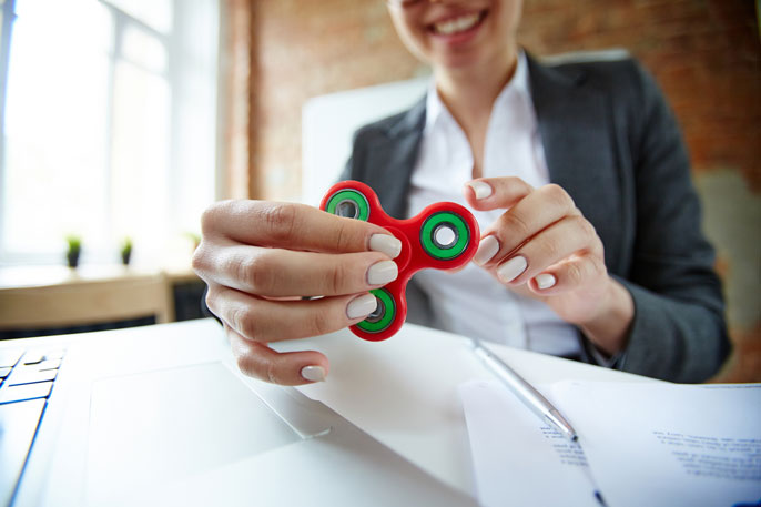Woman in office playing with fidget spinner