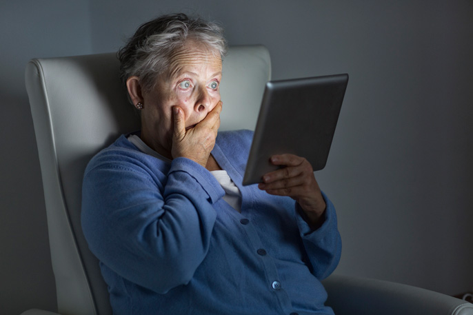 Shocked older woman watching TV on an iPad