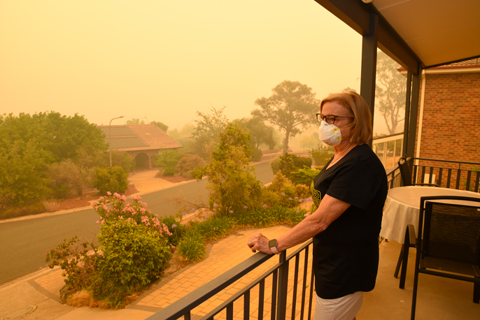 A woman in a mask stares out from her porch at orange air