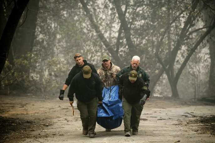 Men carrying a body bag out of a burnt area