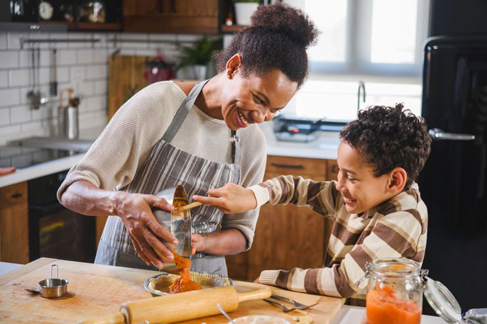 A Black woman baking with her young son