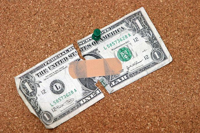 bandaged dollar (Shutterstock)