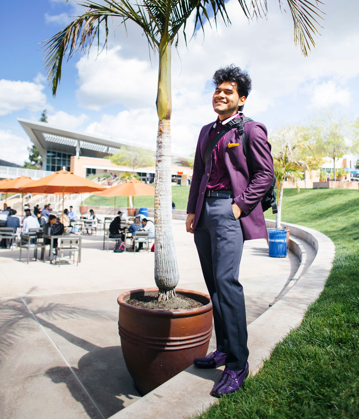 Man in purple suit poses for picture under palm tree