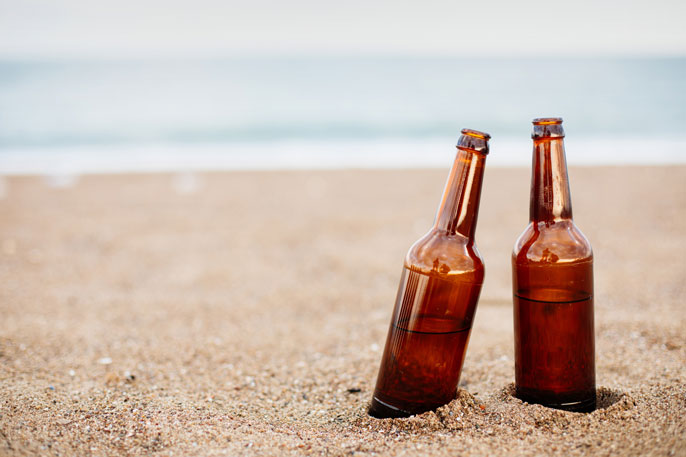 Two half-full beers on a sandy beach