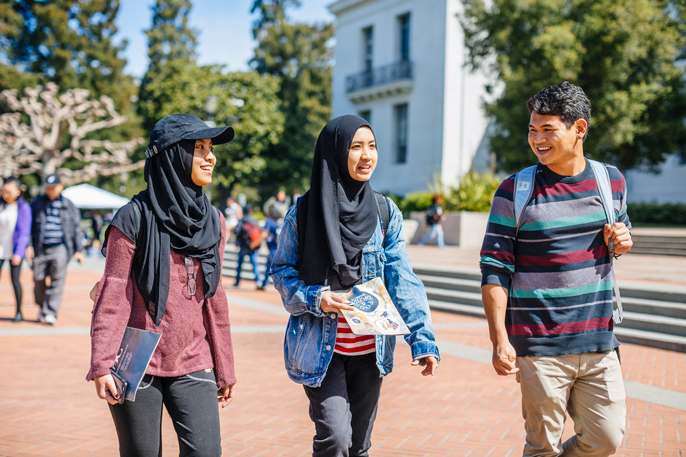 A boy walks next to two fellow students in hijabs on the Berkeley campus