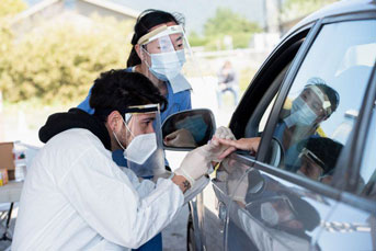 Two clinicians taking blood from a patient's hand held out of car window