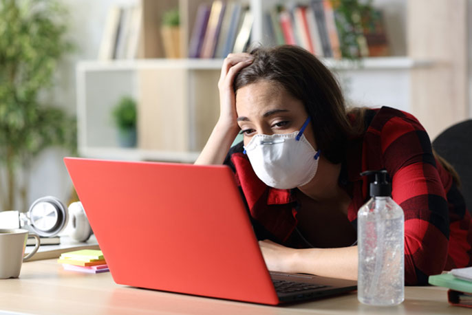 Student in mask looks at computer, bored