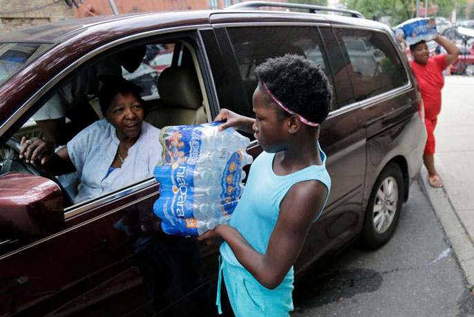 A child holding bottled water speaking to an adult in a car