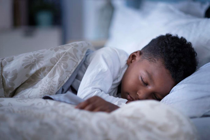 A young boy sleeping under the covers