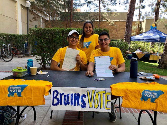 Three UCLA students registering voters at a table