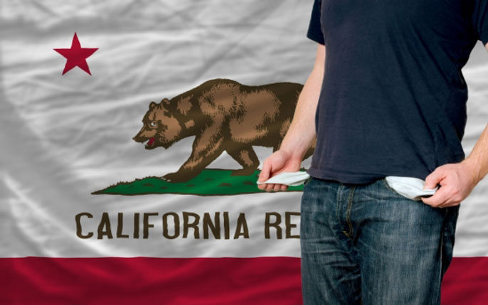 Man exposes empty pockets in front of a California flag