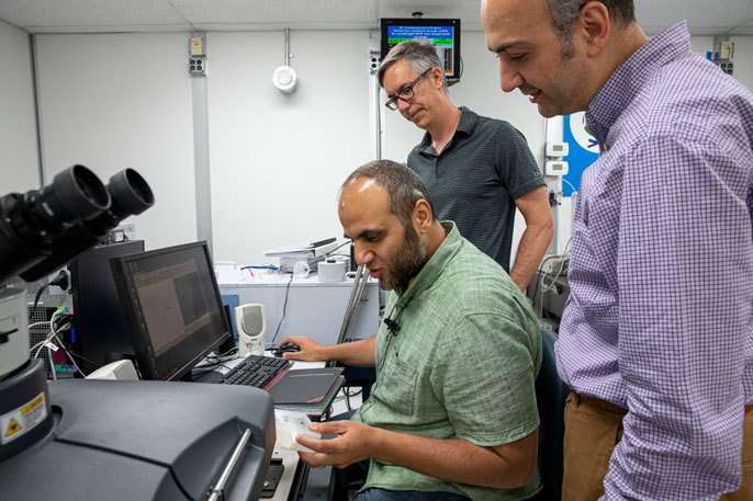 Scientists study bone samples near a computer