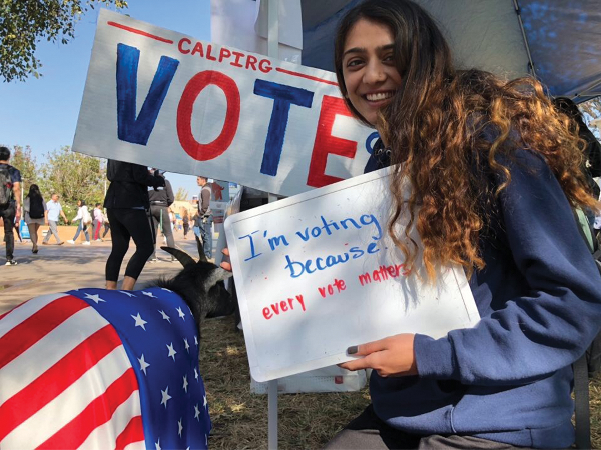 UC Riverside young woman student holds a vote sign next to the vote goat