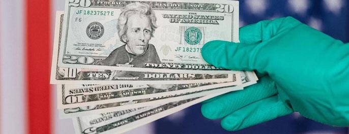 Gloved hand holding $20 bills