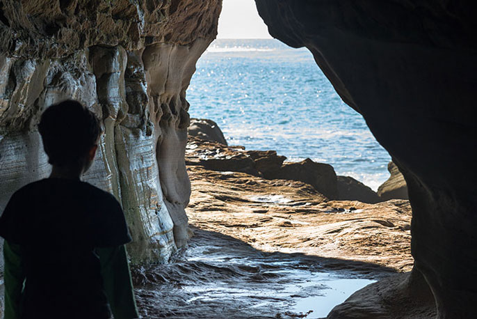 Person looking out from a cave at water