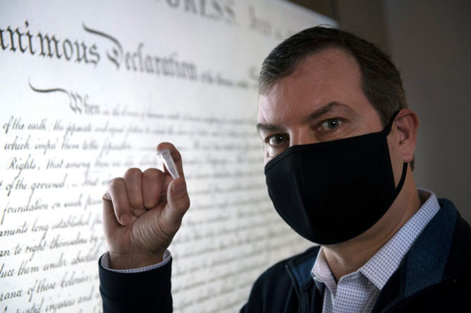 Chaput holds up a small object in front of the Declaration of Independence