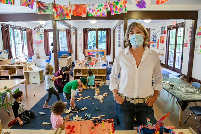 Rockridge Little School owner Holly Gold stands in a classroom with a teacher and busy preschool children