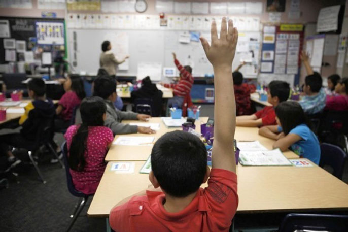 Boy raises hand in classroom Los Angeles Times photo