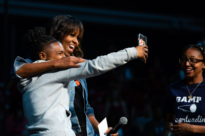 Michelle Obama takes a selfie with a student on College Signing Day