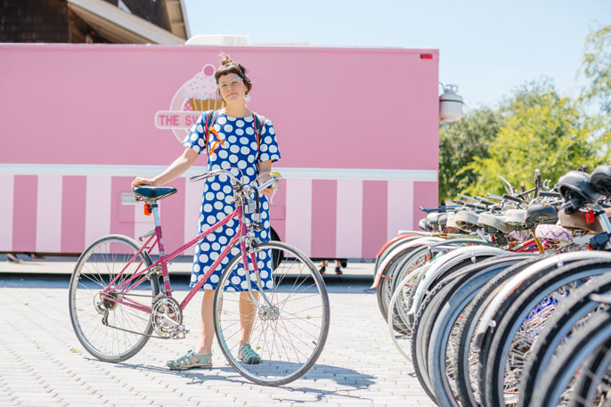 Woman in polka dot dress standing with bike at bike rack