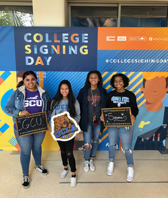 Students posing before the College Signing Day sign