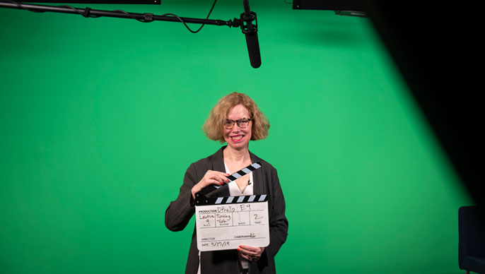 Professor holding a clapperboard