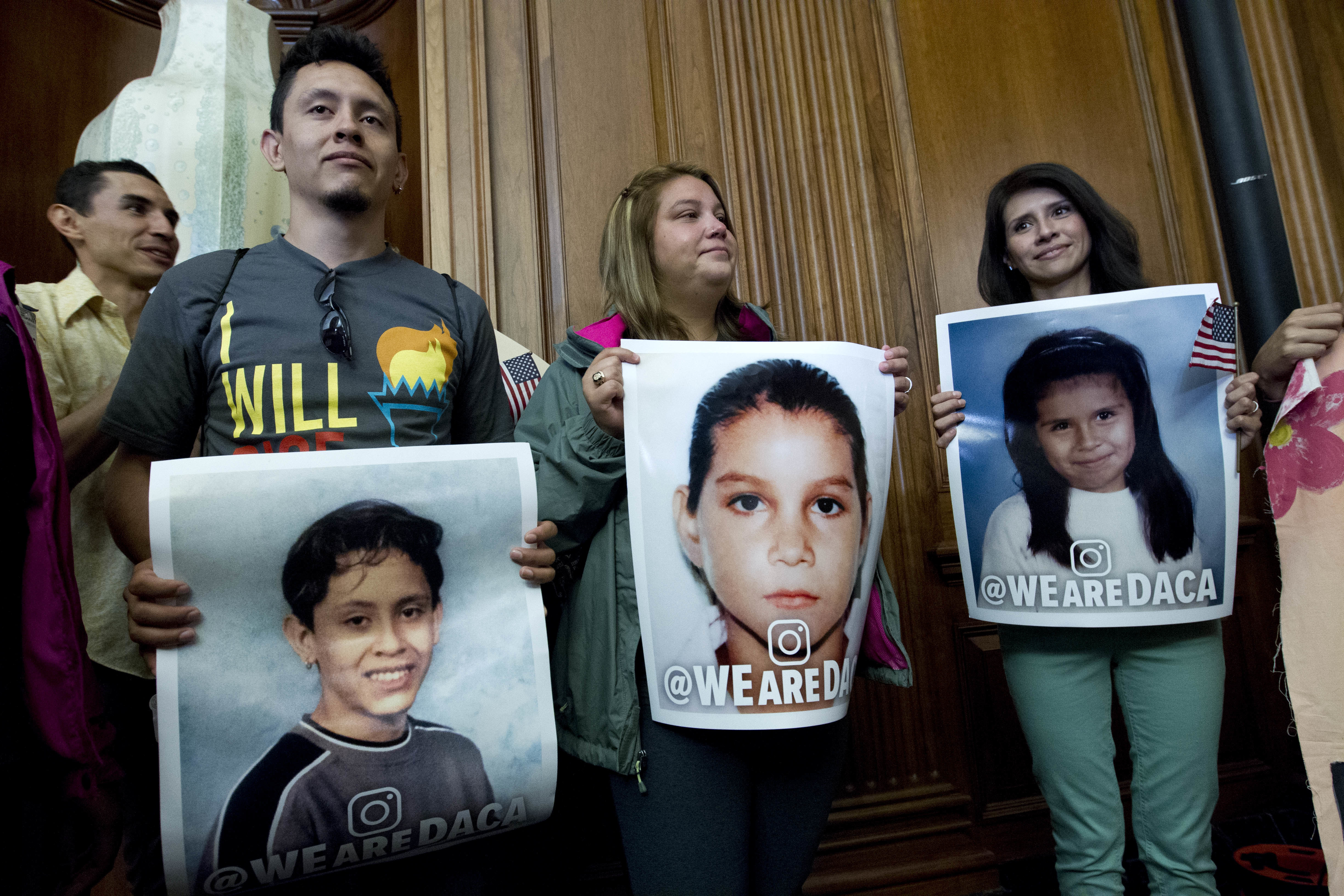 DACA recipients hold pictures of themselves as children during a Congressional meeting