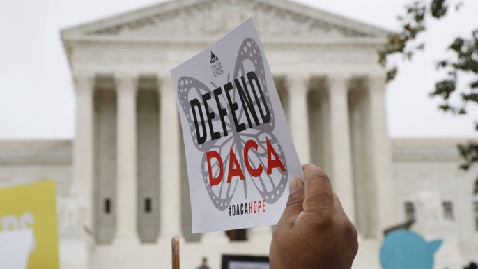 Jacquelyn Martin/AP photo of person holding up a DACA poster