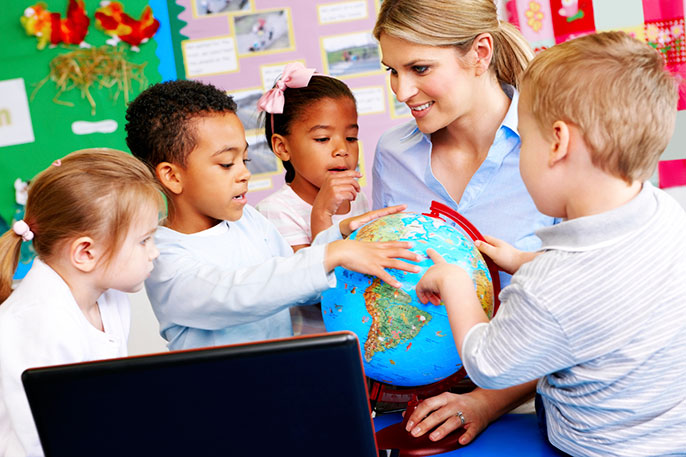 young children and teacher look at globe