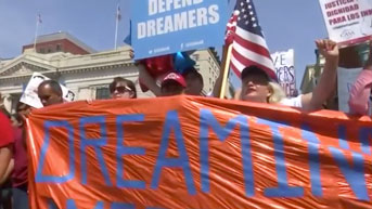 People marching in support of DACA hold a banner. Still from Washington Post/Reuters video