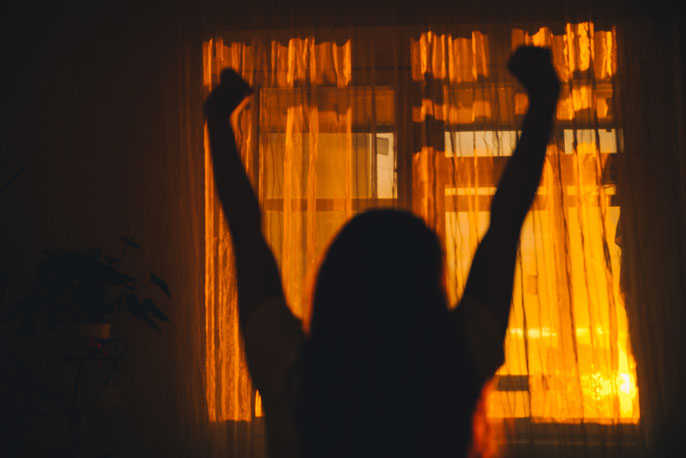 Woman stretching in a room behind curtains that show the dawn