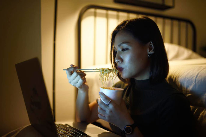A young woman eating noodles at night watching something on the computer