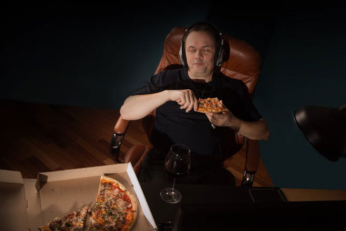 Man in chair eating pizza at night