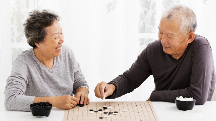 An elderly Asian couple plays a game