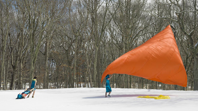 Three people performing with a giant orange sheet outside in the snow