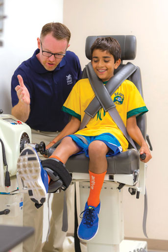 Kid stretching leg with researcher standing by