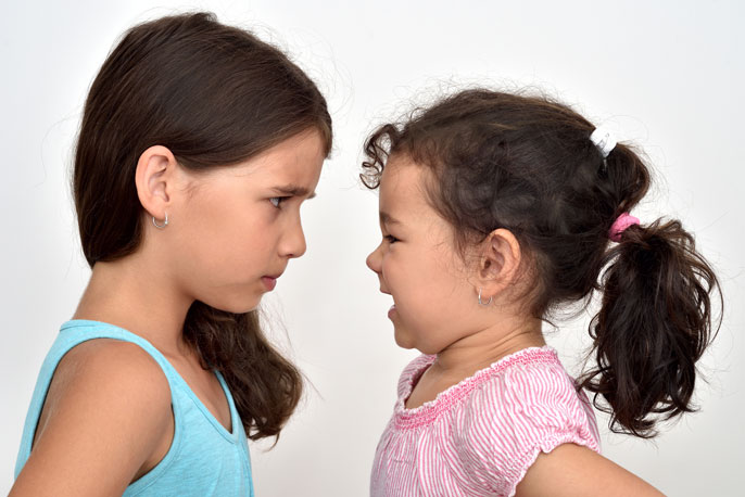 Two little girls look at each other eye to eye, one angry