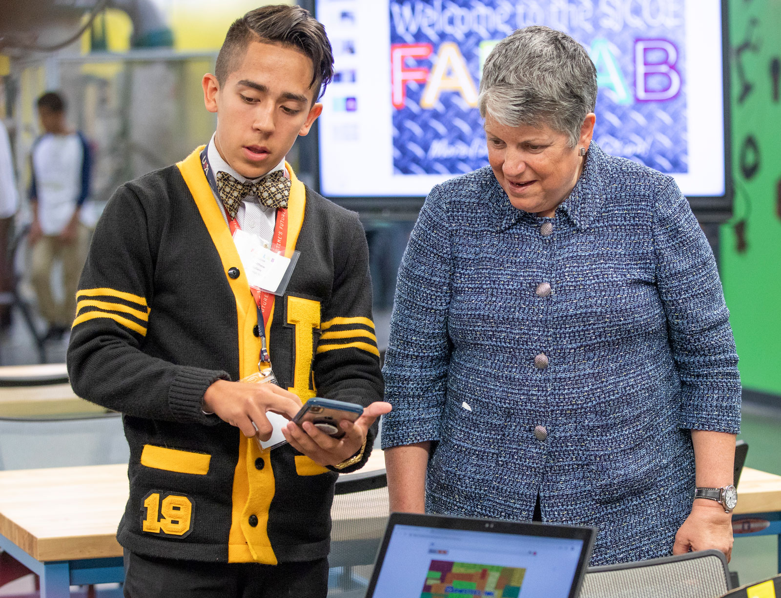 UC President Janet Napolitano stands with a teenager who shows her something on a phone