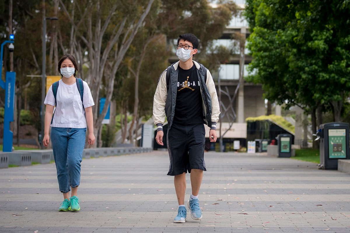 Two students walking with facemasks on