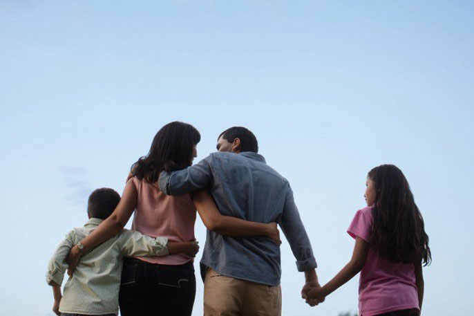 Family walking forward with sky background