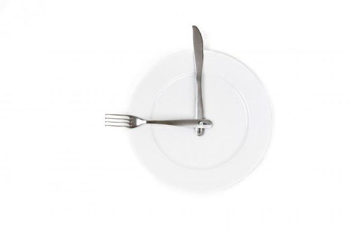 Plate with a fork and knife positioned like hands of a clock