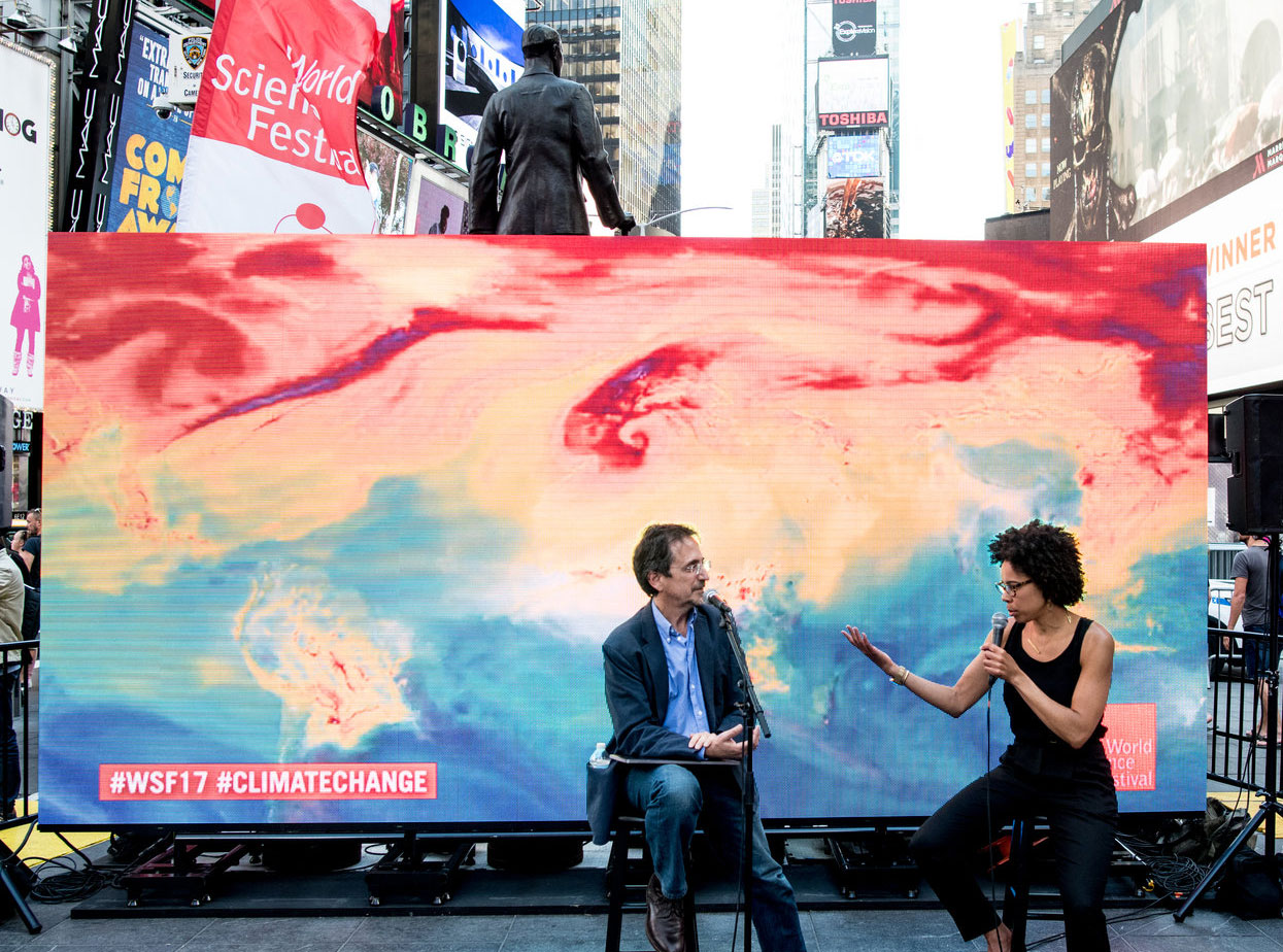Ayana Elizabeth Johnson in front of a colorful backdrop with Andy Revkin in Times Square