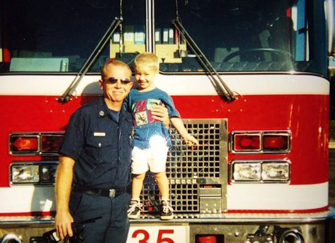 Kelly Richeson in front of fire truck with son