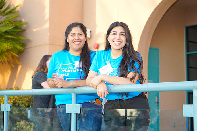 Two attendees of the First Generation conference smiling and leaning on a railing
