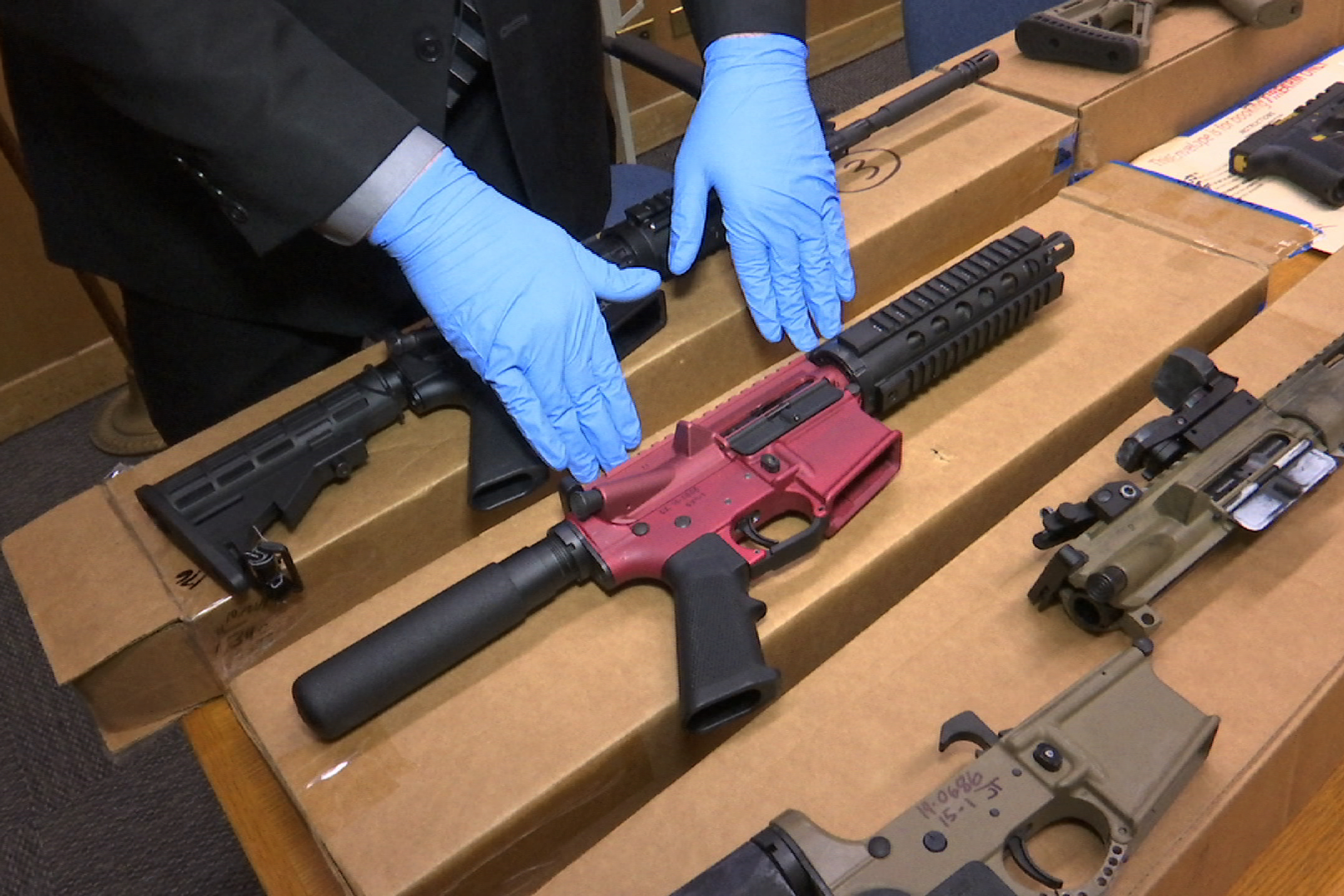 A San Franciso police officer displays several 'ghost guns' – untraceable firearms with no serial numbers or manufacturing marks.